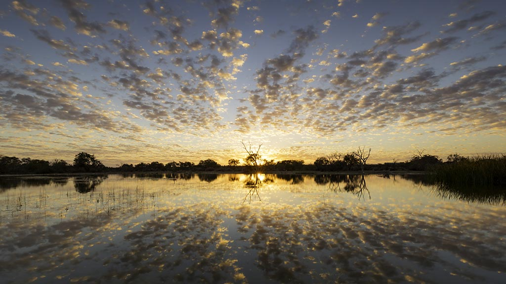 A spectacular sunrise at Muloorina Station reflected in the water just to the north of Marree, South Australia