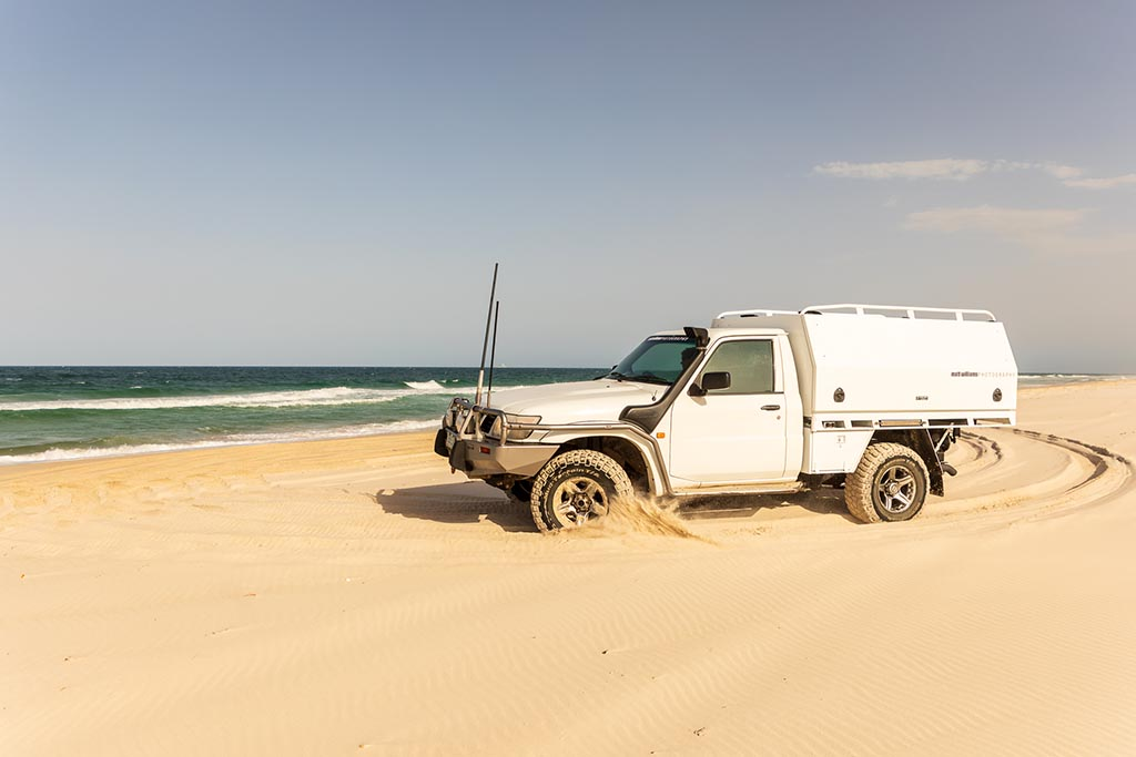 Driving our ute on the beach at Bribie Island