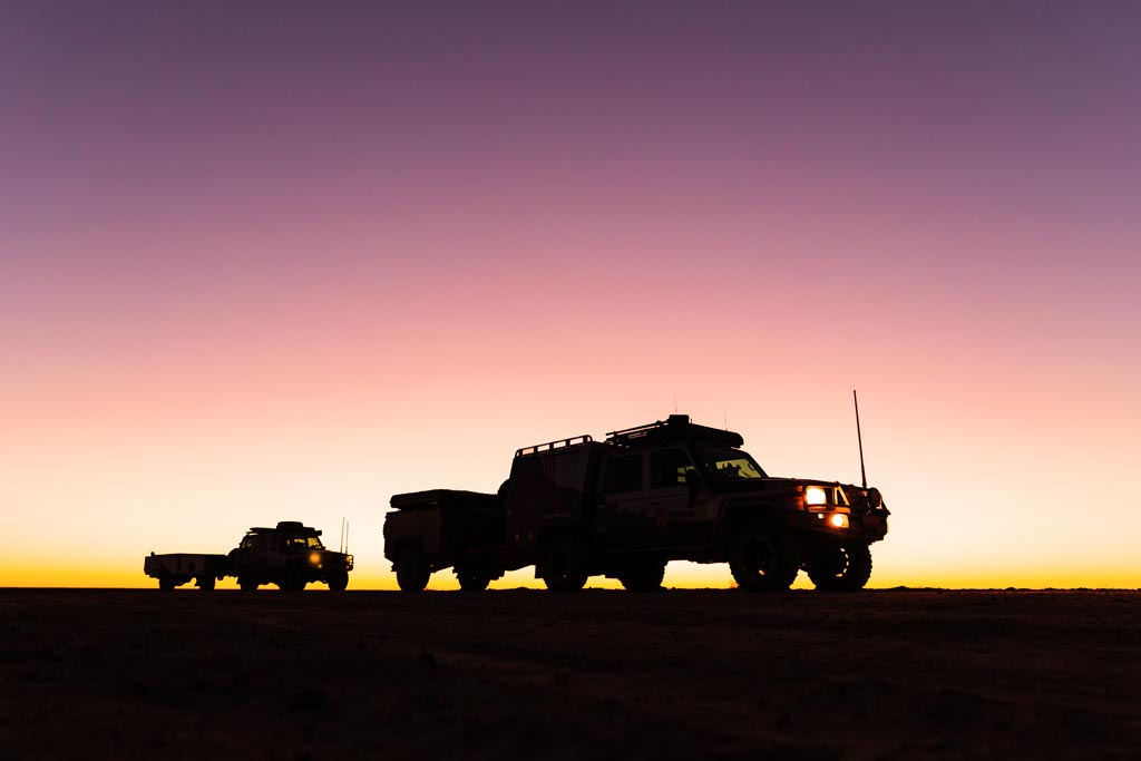 Silhouette of two vehicles at sunrise on the Birdsville Track