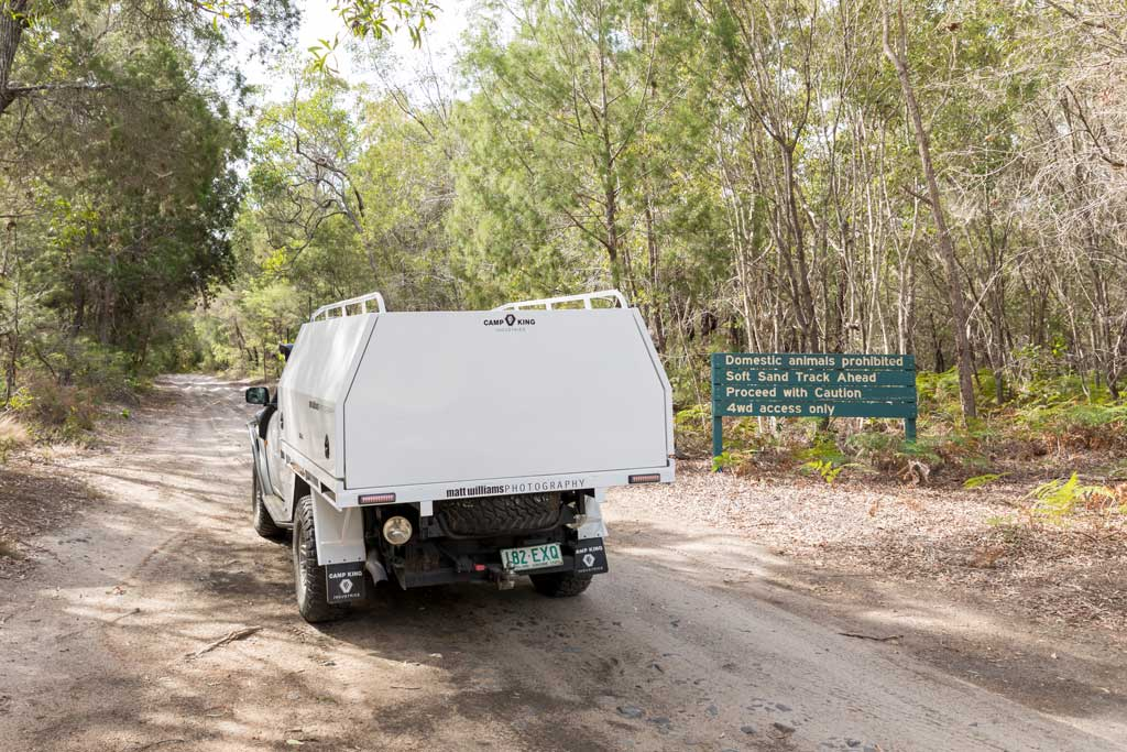 4WD driving along sandy track