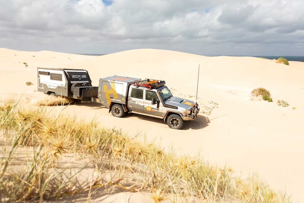 4wd towing a hybrid camper trailer on the sand