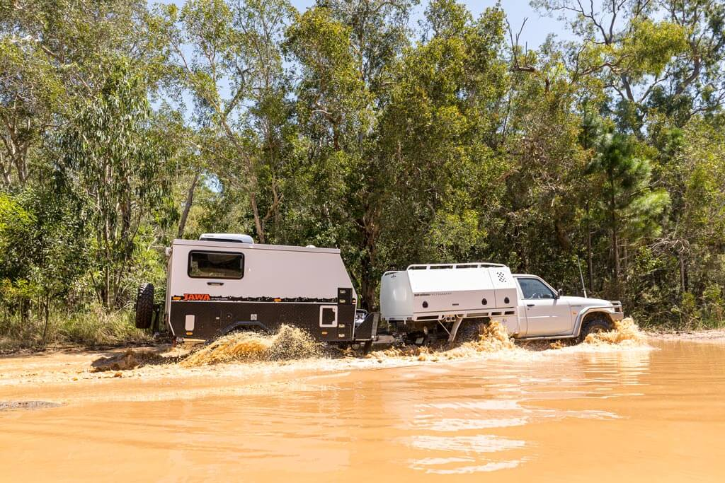 The JAWA TRAX 10 Hybrid Camper Trailer driving through a big puddle