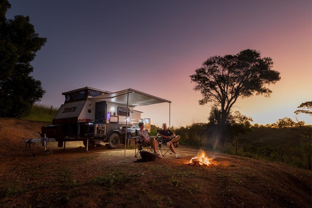 Sitting around a campfire at sunset
