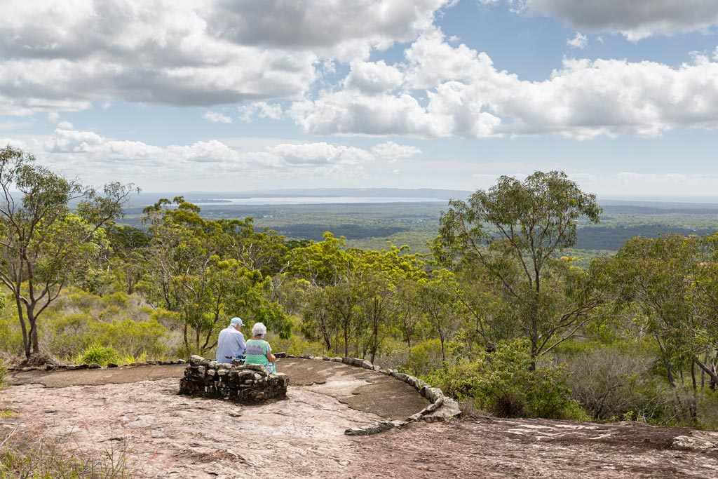 An elderly couple enjoying the views from the lower lookout on Mt Tinbeerwah