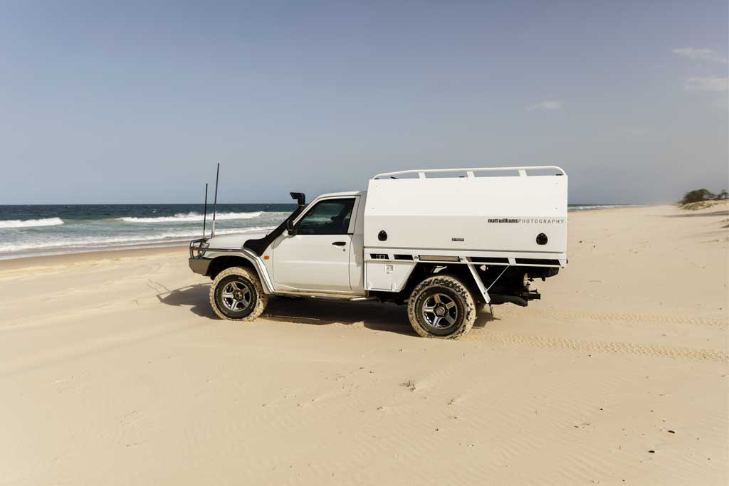 4wd ute parked on the beach - how to drive on sand