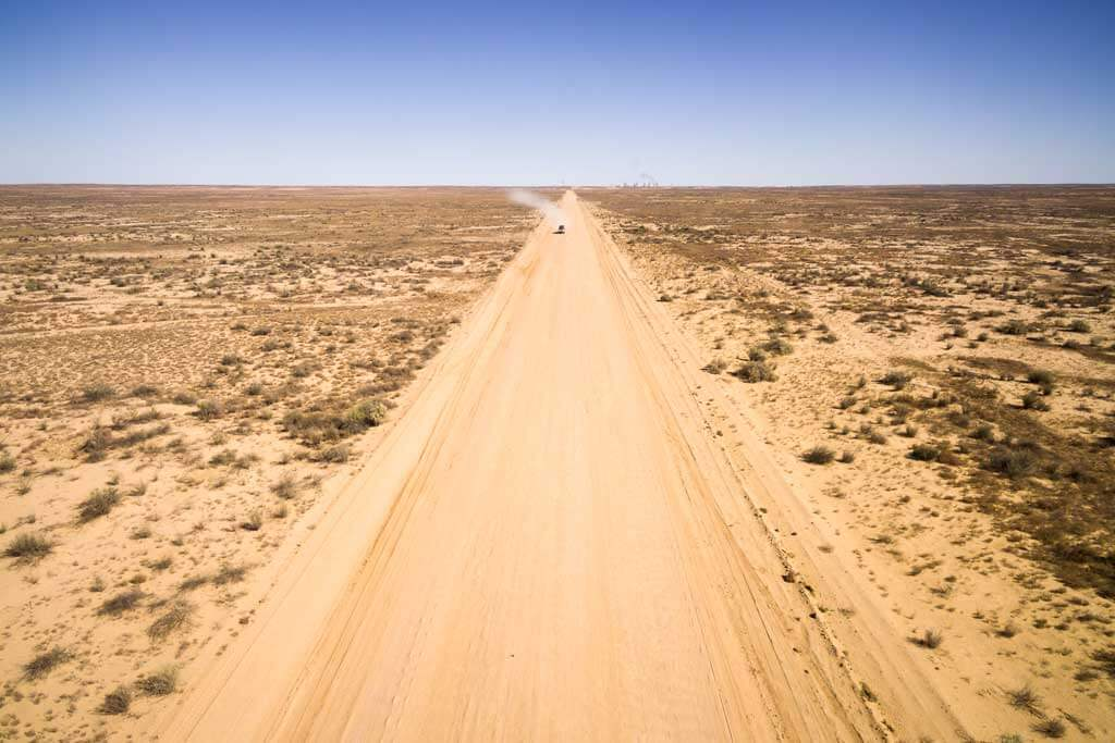 aerial view of 4wd driving along remote outback dirt track