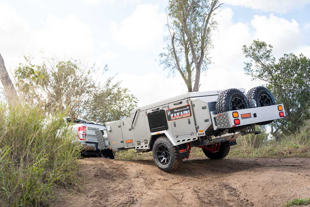 forward fold camper trailer being towed off-road