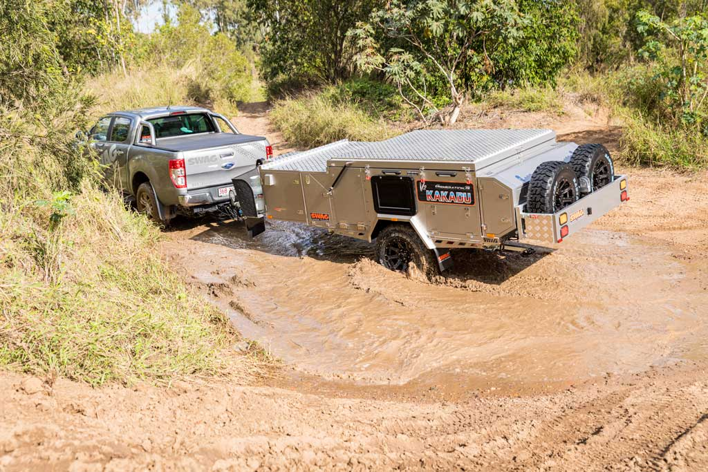 4wd pulling forward fold camper trailer through a muddy puddle