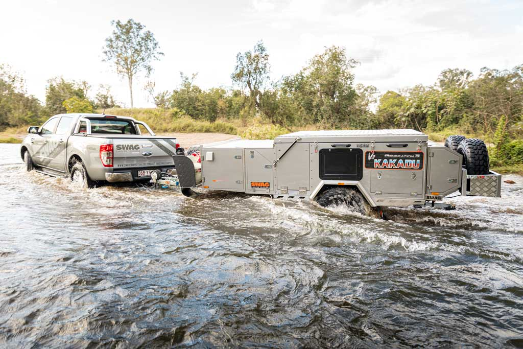4wd pulling forward fold camper trailer through the water