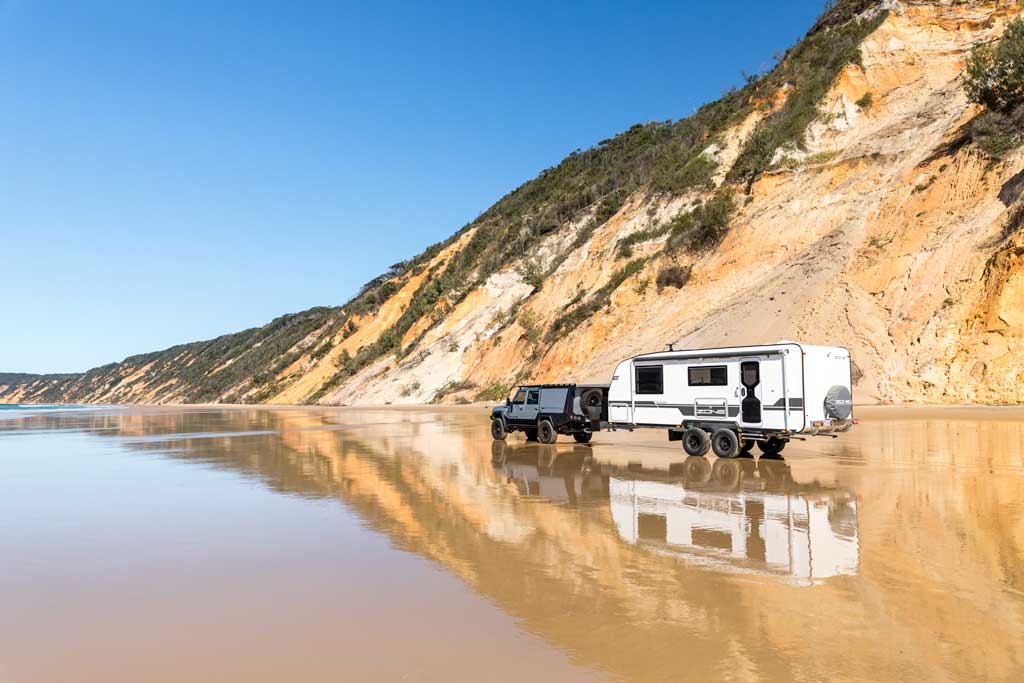 4wd and caravan on the beach with reflections of coloured sands