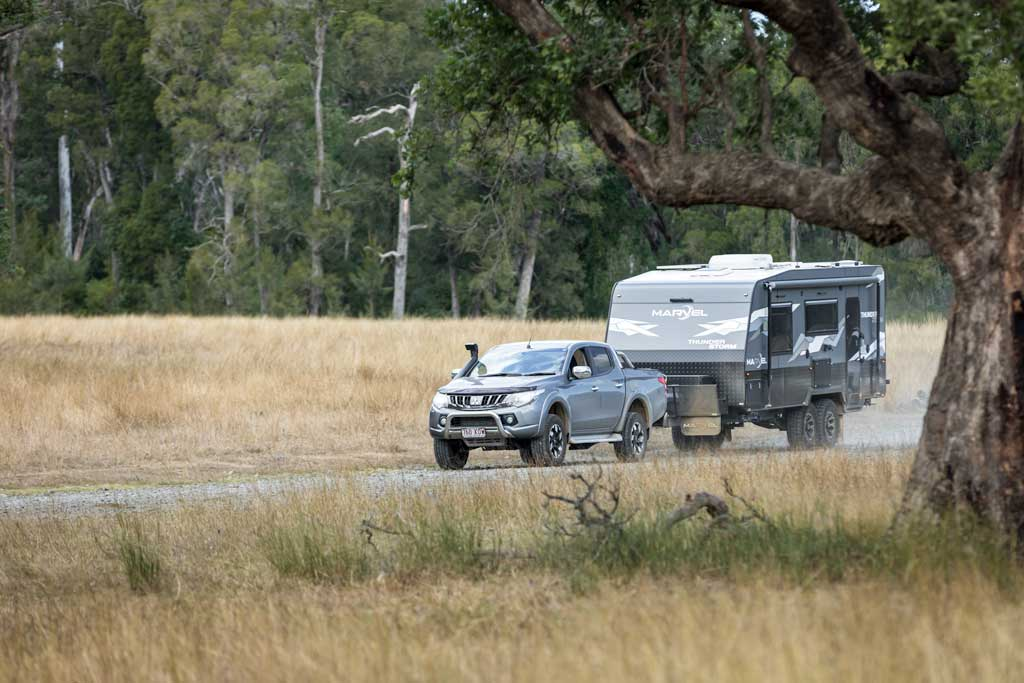 4wd towing caravan along dirt road