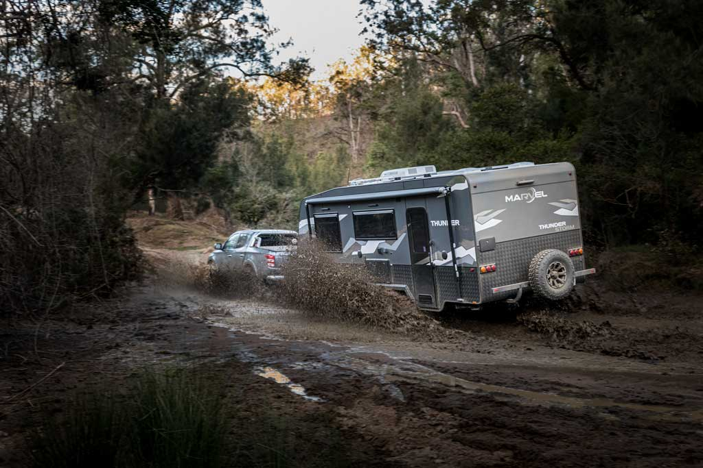 4wd and caravan driving through muddy water