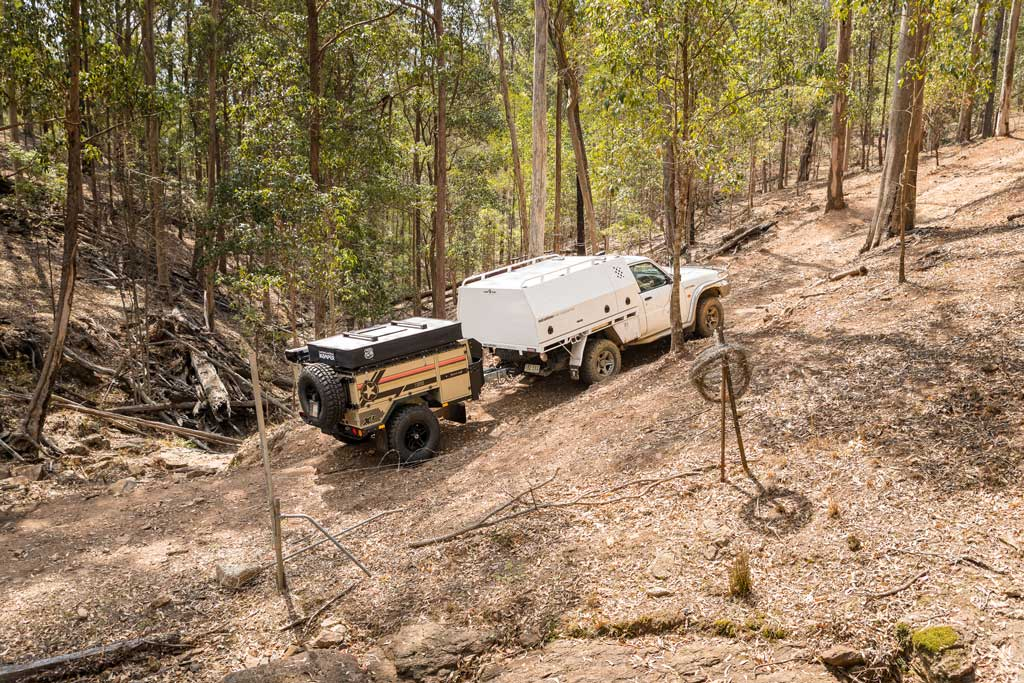 4WD towing camper trailer along dirt track